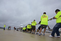 Special Olympics Team Pulls United Airplane at Rainy Chicago O'Hare International Airport. Team working to pul a jumbo jet plane on the runway Royalty Free Stock Photos