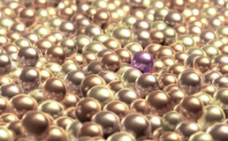 Special pearl. A purple pearl stands out from the other creamy pearls Royalty Free Stock Photography