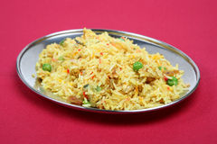 Special Pilau Rice. Pilau rice with peas and spices on a burgundy tablecloth Royalty Free Stock Photo