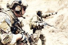 Special reconnaissance team members in desert area. US special operations forces fighters armed with assault rifle, in opscore helmet, radio tactical ops headset stock photo