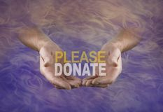 A special request to PLEASE DONATE and help raise funds. Male hands offering the word PLEASE DONATE emerging from a wispy gaseous indigo and peach coloured smoke Stock Photos