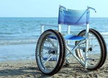 Special rullstol med hjul och gummihjul som går in i havet Arkivbild