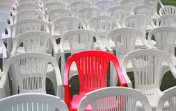 Special seat. One red chair among many white plastic chairs.  Special, or reserved seating Stock Images