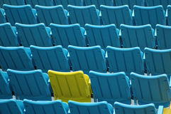 Special seat. A special yellow seat among rows od blue seats Stock Photography