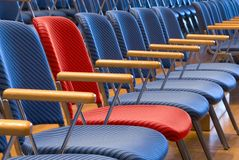 The special seat. Single red seat in a row of blue seats stock image