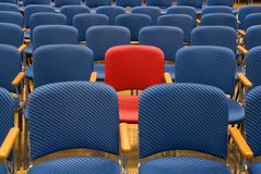 The special seat. Single red seat in the middle of rows of blue seats royalty free stock images