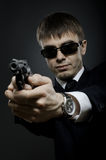 Special-service agent. Portrait  the  beautiful  man in black costume,  special-service agent or  body guard with  pistol Royalty Free Stock Photos