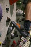 Special shoes made for bouldering on a grip at the wall stock image