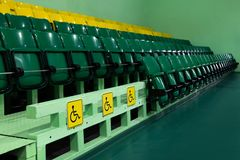 Special signs for places with disabilities. Audience for viewers. Green and yellow rows with plastic folding seats. Perspetiva. stock photo