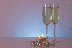 Special tinted photo of greeting card template made of two glasses of champagne with two candles, christmas balls and  string of b Royalty Free Stock Photo