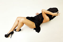 Special toned photo of female body in black silk fabric and in high heels shoes luing on floor. Horizontal view Royalty Free Stock Photos