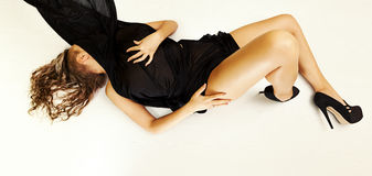 Special toned photo of female body in black silk fabric and in high heels shoes luing on floor. Horizontal view Stock Photos