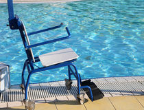 Special wheelchair for handicapped by the pool Royalty Free Stock Image