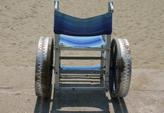 Special wheelchair to move around on the sand of the beach in su Royalty Free Stock Photography
