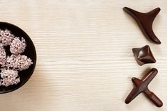 Special wooden massage sticks lying in row, bowl with flowers on wooden background with copy space. SPA and massage concept. Special carved wooden massage stock photography