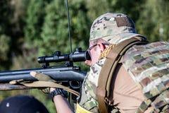 Speciale krachten, het geweer van de militairaanval met knalpot, optisch gezicht achter dekking die in hinderlaag wachten royalty-vrije stock afbeeldingen
