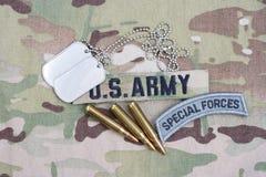 Specialförband för USA-ARMÉ tab, flaggalappen, med hundetiketten och 5 56 mmrundor på kamouflagelikformign Arkivbilder