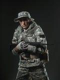 Specialförband tjäna som soldat mannen med maskingeväret på en mörk bakgrund Fotografering för Bildbyråer