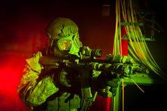 Specialförbandsoldat med gasmasken under nattbeskickning Royaltyfri Bild