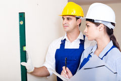 Specialist and assistant working with wall in new building Stock Images