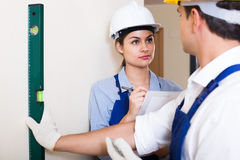 Specialist and assistant working with wall in new building Royalty Free Stock Photo