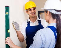 Specialist and assistant working with wall in new building Stock Photography
