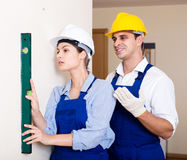 Specialist and assistant working with wall in new building Royalty Free Stock Images