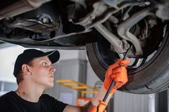 Specialist auto mechanic in the car service. Check a transmition. Specialist auto mechanic in the car service repairs the car stock photography