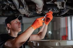 Specialist auto mechanic in the car service. Specialist auto mechanic in the car service repairs a car royalty free stock photo