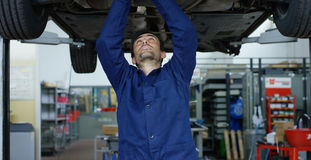 Specialist auto mechanic in the car service, repairs the car, makes transmission and wheels. Concept: repair of machines, fault di stock photo