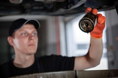 Specialist auto mechanic in the car service. Specialist auto mechanic in the car service repairs the car. Replacing the oil filter stock photos