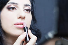 Specialist in beauty salon gets lipstick, lip gloss, professional make-up. Stock Photo