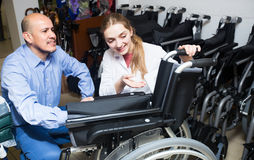 Specialist consulting client about wheelchairs. Specialist consulting elderly client about mechanical wheelchairs Royalty Free Stock Photo