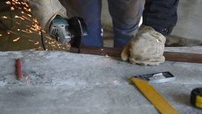 Specialist cut rectangular metal profile using angle grinder. People at work, profession and skill. Work process closeup stock video