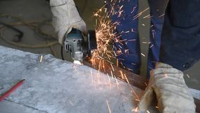 Specialist cutting rectangular metal profile using the electric angle grinder, skills and competence, sparks fly around. Specialist cutting rectangular metal stock video