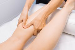 The specialist does massage of the knees to the client of the ma royalty free stock photography