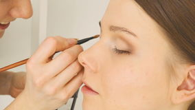 Specialist doing makeup for model. Gentle make-up for the young girl. stock video footage