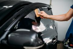 Specialist with drier, tinting film installation. Male specialist with drier, car tinting film installation process, tinted auto glass installing procedure Stock Photography