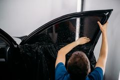 Specialist with drier, tinting film installation. Male specialist with drier, car tinting film installation process, tinted auto glass installing procedure Royalty Free Stock Photo