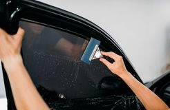 Specialist with drier, tinting film installation Royalty Free Stock Photo