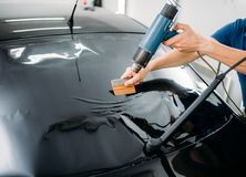 Specialist with drier, tinting film installation. Male specialist with drier, car tinting film installation process, tinted auto glass installing procedure Stock Image