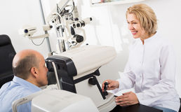 Specialist examinating eye with aid of slit lamp Royalty Free Stock Image