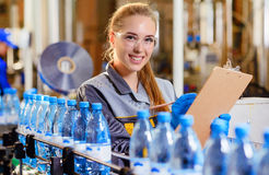 Specialist in factory checking bottles. Young happy female worker at factory checking bottles with pure water Stock Image