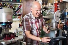 Specialist fixing heel taps. Friendly elderly specialist fixing heel taps of shoes on machine Stock Photos