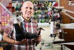 Specialist fixing heel taps. Friendly elderly smiling specialist fixing heel taps of shoes on machine Royalty Free Stock Photos