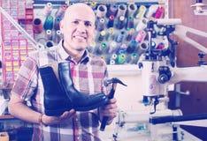 Specialist fixing heel taps. Friendly elderly smiling specialist fixing heel taps of shoes on machine Stock Images