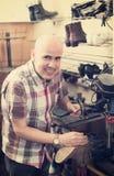Specialist fixing heel taps. Positive senior specialist fixing heel taps of shoes on machine Stock Photography