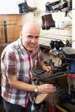 Specialist fixing heel taps. Positive senior specialist fixing heel taps of shoes on machine Stock Photos