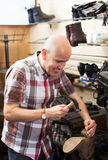 Specialist fixing heel taps Royalty Free Stock Photography