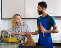 Specialist fixing leaky faucet, pleased cheerful blonde Royalty Free Stock Photos